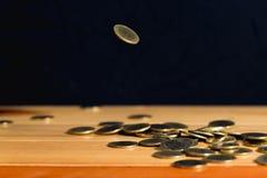 El dinero de las monedas de oro que cae en la tabla de madera con la pared negra, copia s Fotografía de archivo