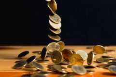 El dinero de las monedas de oro que cae en la tabla de madera con la pared negra, copia s Fotos de archivo libres de regalías