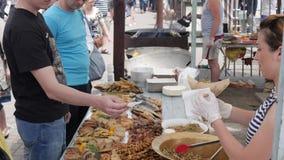 El dinero en las manos del comprador, comida justa en la calle, efectivo de mano a mano en el mercado, pago en la comida basura,  almacen de metraje de vídeo