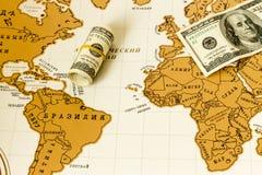 El dinero está en el mapa del mundo Fotografía de archivo