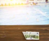 El dinero euro en el fondo de la TV por alguien muestra el water polo, deportes apostando, euro foto de archivo libre de regalías