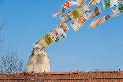 El dinero euro vuela encima de la chimenea Imágenes de archivo libres de regalías