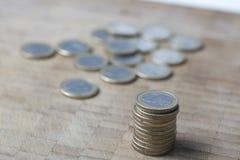 El dinero europeo un euro acuña en un fondo de madera Fotos de archivo