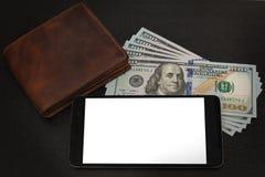El dinero, la cartera y el teléfono celular mienten en una tabla Fotos de archivo