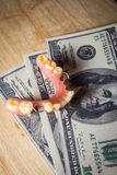 El dinero pagado para los dientes cuida, artificial con la nota del dólar Foto de archivo