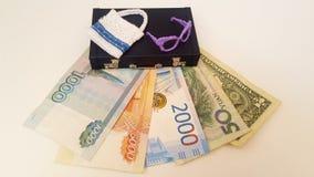 El dinero para el viaje está debajo de la maleta Billetes de banco de diversos países imagen de archivo libre de regalías