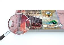 el dinero rendido 3D de Kuwait con la lupa investiga moneda en el fondo blanco Imágenes de archivo libres de regalías
