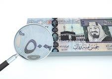 el dinero rendido 3D de la Arabia Saudita con la lupa investiga moneda en el fondo blanco Foto de archivo libre de regalías