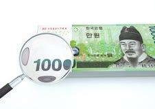 el dinero rendido 3D de la Corea del Sur con la lupa investiga moneda en el fondo blanco Fotos de archivo libres de regalías