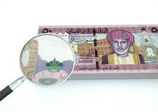 el dinero rendido 3D de Omán con la lupa investiga moneda en el fondo blanco Foto de archivo libre de regalías