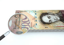 el dinero rendido 3D de Venezuela con la lupa investiga moneda aislada en el fondo blanco Foto de archivo libre de regalías