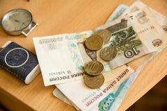 El dinero y el reloj rusos mienten en una tabla de madera Imagenes de archivo