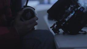 El director con la estación de radio portátil se sienta en el primer de la pantalla almacen de video