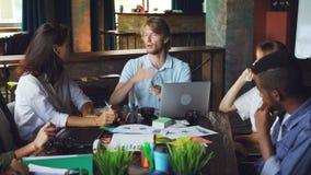 El director hermoso del hombre joven está hablando con sus empleados y está gesticulando sentarse en el escritorio en oficina mod almacen de metraje de vídeo