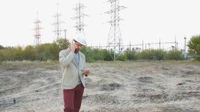 El director técnico de la estación en un casco blanco se coloca cerca de la central eléctrica y de hablar en el teléfono con los  almacen de video