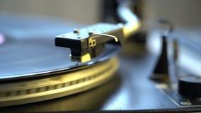 El disco de vinilo en cierre del tocadiscos de la placa giratoria de DJ para arriba La placa y la aguja giratorias con el primer  almacen de metraje de vídeo