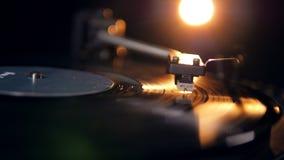 El disco de vinilo está jugando en la luz artificial metrajes