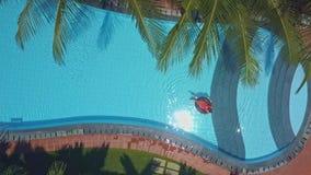 El disco del sol del mediodía refleja en agua azul de la piscina con la muchacha metrajes