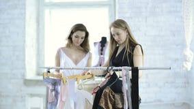 El diseñador ayuda a mujeres hermosas a elegir la ropa interior en suspensiones metrajes