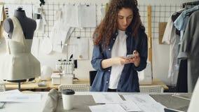 El diseñador bonito de la ropa está eligiendo los bosquejos para el plano puesto entonces tomando imágenes con smartphone Puesta  almacen de metraje de vídeo