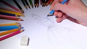 El diseñador con un bosquejo del lápiz adorna los vestidos en azul Cierre para arriba almacen de video