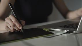 El diseñador de la mujer dibuja en una tableta de gráficos