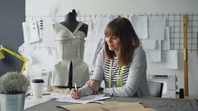 El diseñador de la ropa en pequeño negocio de lanzamiento está dibujando los bosquejos para la ropa del ` s de las mujeres y está metrajes