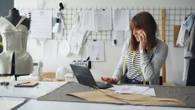 El diseñador de la ropa está discutiendo bosquejos de la ropa en el teléfono móvil y la información que entra en ordenador portát almacen de metraje de vídeo