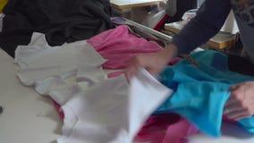 El diseñador de la ropa está trabajando con medidas en una tabla del estudio 4k UHD almacen de video