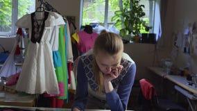 El diseñador de la ropa está trabajando con medidas en una tabla del estudio 4k UHD almacen de metraje de vídeo