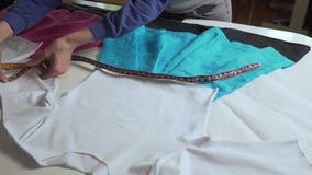 El diseñador de la ropa está trabajando con medidas en una tabla del estudio 4k UHD metrajes