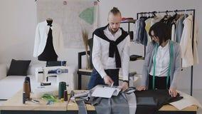 El diseñador de la ropa y de la modista desarrolla una nueva colección de ropa en el pequeño taller moderno acertado almacen de metraje de vídeo