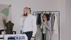 El diseñador de moda o la modista profesional que toma las medidas para el traje de costura en los sastres hace compras Costurera metrajes