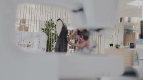 El diseñador de moda ocupado enrolla el maniquí con el vestido lujoso negro y perfora o pincha la tela con metrajes