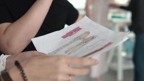 El diseñador de moda, el sastre y la modista jovenes trabaja con un ayudante y mira el bosquejo de la ropa almacen de video