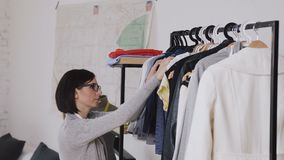 El diseñador de moda de sexo femenino trabaja en la nueva colección para los clientes en estudio acogedor del taller, la modista, metrajes