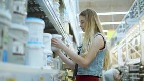El diseñador de sexo femenino está examinando los potes con las pinturas en una tienda, tomando diferentes tipos metrajes