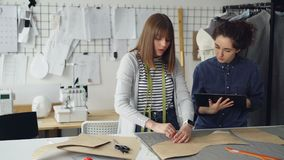 El diseñador de sexo femenino de la ropa está dibujando esquemas de la nueva ropa en tela con tiza mientras que su colega le está almacen de video