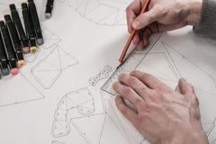 El diseñador de sexo masculino hace un dibujo de trabajo Lugar de trabajo de un diseñador del juguete Los marcadores, la regla, l imagen de archivo