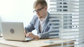 El diseñador del hombre joven en vidrios trabaja en una tableta gráfica almacen de metraje de vídeo