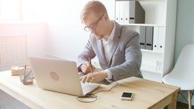 El diseñador del hombre joven en vidrios trabaja en una tableta gráfica almacen de video