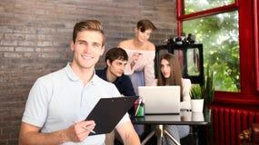 El diseñador en ropa casual es el sentarse, mirando la cámara y sonriendo, sus colegas están trabajando en el fondo Imagenes de archivo