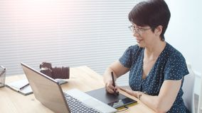 El diseñador gráfico envejeció a la mujer que usaba la tableta gráfica digital mientras que trabajaba en la oficina moderna almacen de video