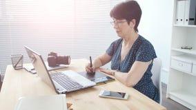El diseñador gráfico envejeció a la mujer que usaba la tableta gráfica digital mientras que trabajaba en la oficina moderna metrajes
