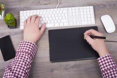 El diseñador gráfico utiliza una tableta digital de la pluma fotografía de archivo libre de regalías