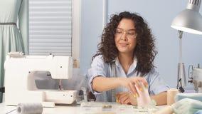 El diseñador joven creativo comienza su día laborable, se sienta en su escritorio en el estudio casero metrajes