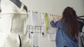 El diseñador joven de la ropa está mirando bosquejos y dibujos colgantes en la pared en taller ligero Colección grande de almacen de metraje de vídeo