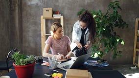 El diseñador joven está dibujando imágenes en el cuaderno que se sienta en la tabla mientras que el fotógrafo de sexo femenino es almacen de video