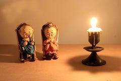 El diseño y la vela clásicos de localización de la silla de la muñeca preciosa del abuelo con la vela ligera entonan iluminación  Fotos de archivo libres de regalías