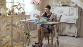 El diseñador de la ropa y la mujer jovenes de la costurera trabajan con la máquina de coser en estudio del sastre almacen de video